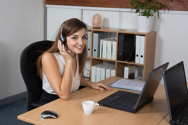Beautiful businesswoman with headphones working at desk