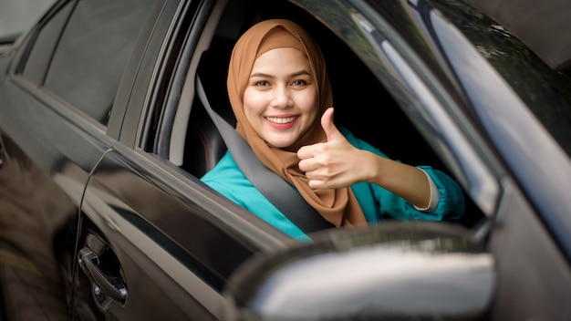 Beautiful businesswoman with hijab is smiling in her car