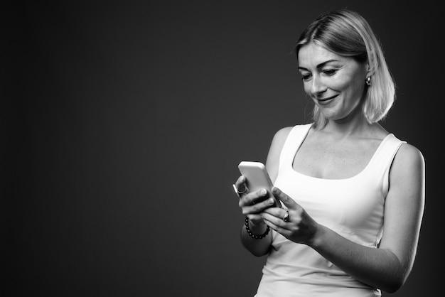 Красивая деловая женщина с короткими волосами с помощью мобильного телефона