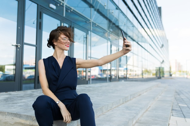 Beautiful businesswoman with smartphone, portrait of a successful manager on the background of a skyscraper