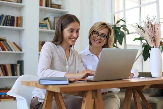 Красивая деловая женщина работает вместе, сидя на столе в офисе.
