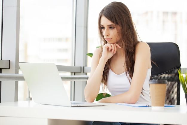 Beautiful businesswoman working on laptop in bright modern office.