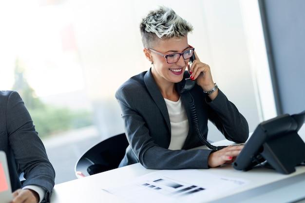 オフィスの彼女の机に座って働く美しい実業家