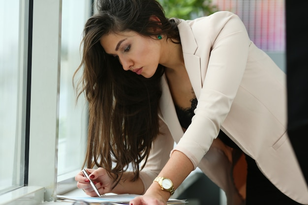 Beautiful businesswoman working with documents in office