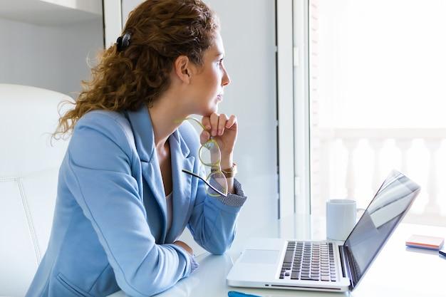 Bella donna d'affari che lavora con il suo computer portatile in ufficio.