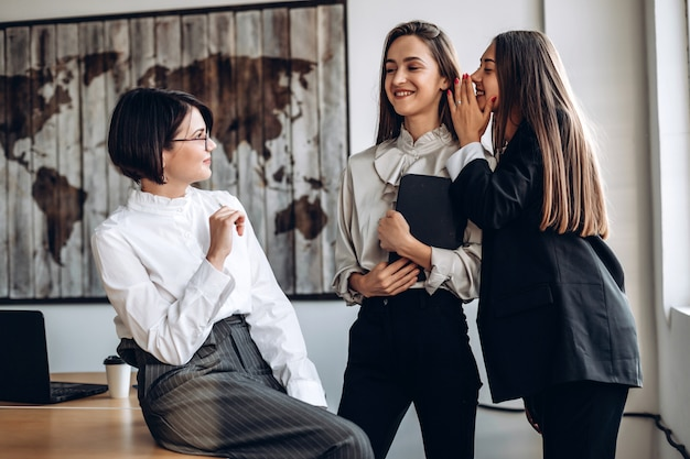 Beautiful businesswomen discuss and whisper to each other