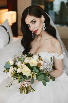 Beautiful and busty brunette model girl with bright makeup and with luxury big earrings with diamonds in a fashionable wedding dress holding a big bouquet of flowers in her hands