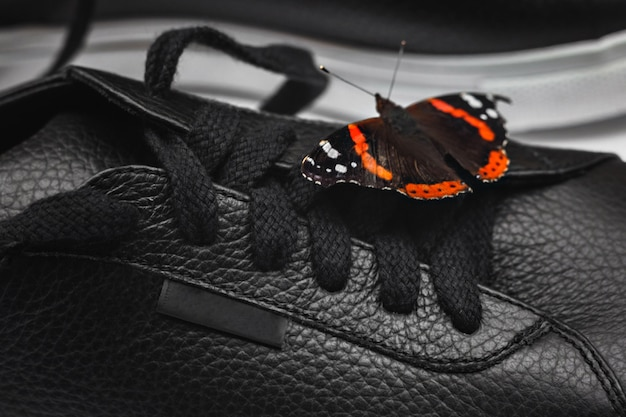 Beautiful butterfly on black leather sneakers. blogger or stylish concept. selective focus. close up