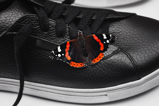 Beautiful butterfly on black leather sneakers. natural and stylish concept. selective focus. close up