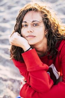 Красивая какуазийская модель, задумчивая в одиночестве на пляже во время досуга на свежем воздухе