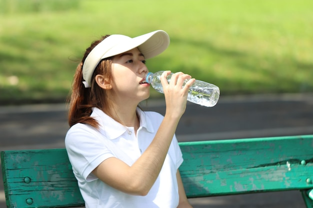A beautiful caddy sits and drinking water on a green chair in a golf course shes relax after do work in the next round sport concept