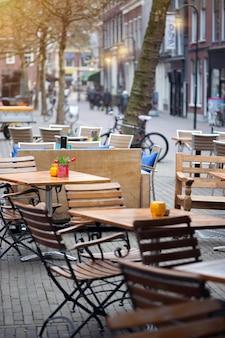 オランダの街デルフトの通りにある美しいカフェ。通りのテーブルと椅子
