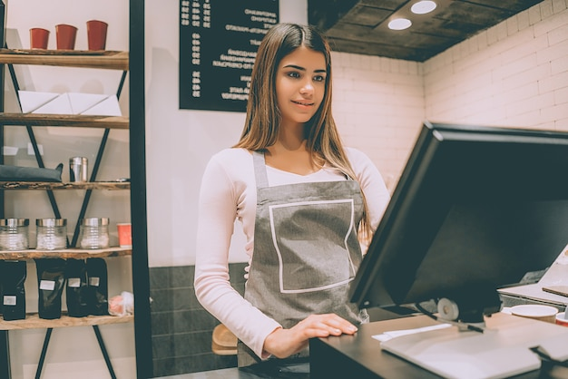 The beautiful cafe worker standing behind the cash register