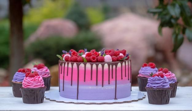 여름 정원에서 흰색 나무 테이블에 분홍색과 보라색 크림과 함께 아름다운 케이크와 컵 케이크
