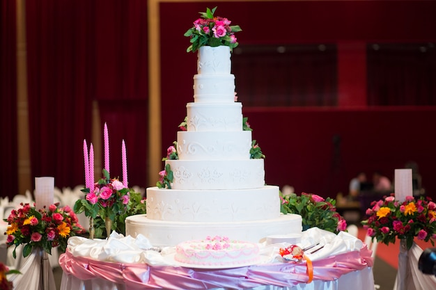 Beautiful cake decorate with pink rose, flower and candle for wedding ceremony
