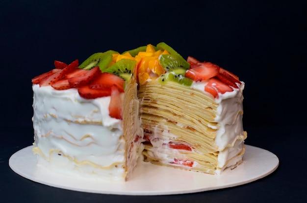 カラフルな果物で飾られた美しいケーキカットスライス暗い背景