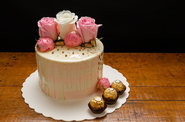 나무 테이블에 천연 장미와 초콜릿으로 장식된 아름다운 케이크