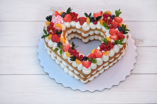 Beautiful cake in the form of a heart with cheese cream and berries