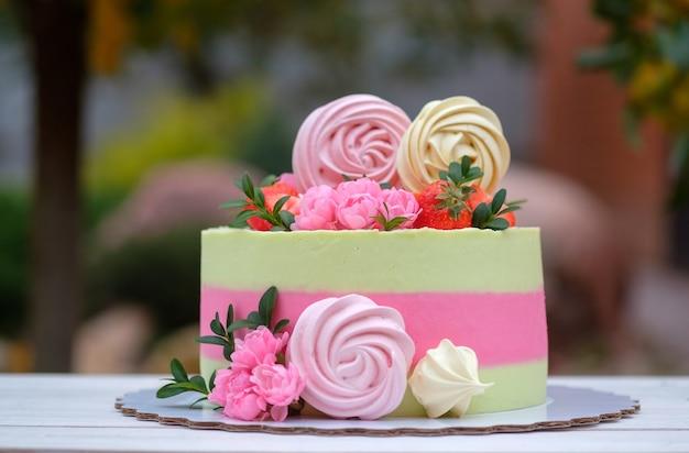 가을 정원의 테이블에 신선한 꽃, 딸기 및 머랭으로 장식 된 섬세한 크림 노란색과 분홍색 크림이있는 아름다운 케이크