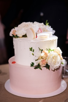 Beautiful cake with macarons and roses stands on the table
