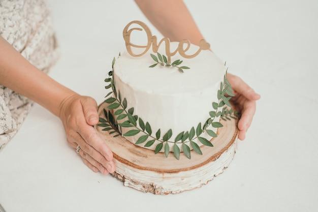 緑の葉と白いクリームチーズの美しいケーキ1年の赤ちゃんミニマリストのための手作りケーキ...