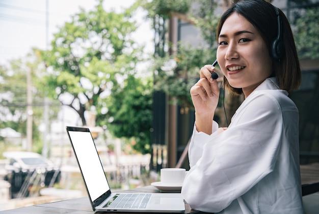 아름다운 콜센터 직원이 음성 서비스 마인드와 정보 녹음 기술을 갖춘 외부 citypark professional에서 헤드폰 및 마이크 케이블을 통해 고객에게 이야기하고 서비스를 제공합니다.