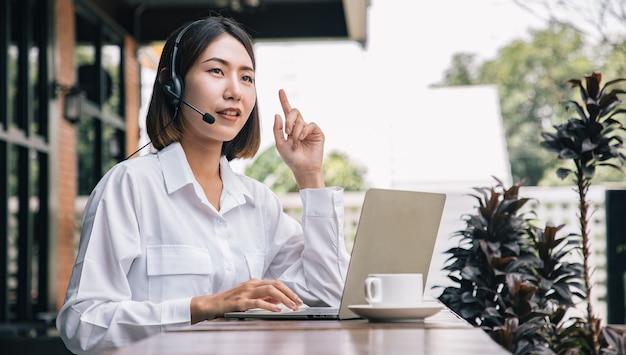 아름다운 콜센터 직원이 도시 밖에서 헤드폰과 마이크 케이블을 통해 고객에게 이야기하고 서비스를 제공합니다. 음성 서비스 마인드와 정보 녹음 기술을 갖춘 전문가