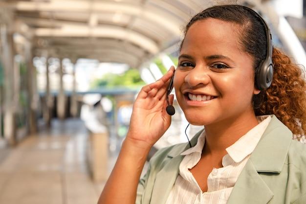 아름다운 콜센터 직원이 외부 도시 풍경에서 헤드폰과 마이크 케이블을 통해 고객에게 이야기하고 서비스를 제공합니다.