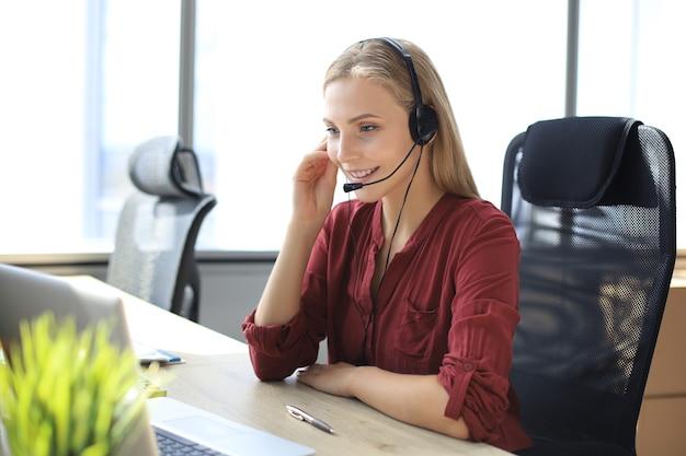 헤드폰을 끼고 있는 아름다운 콜센터 직원이 현대적인 사무실에서 일하고 있습니다.