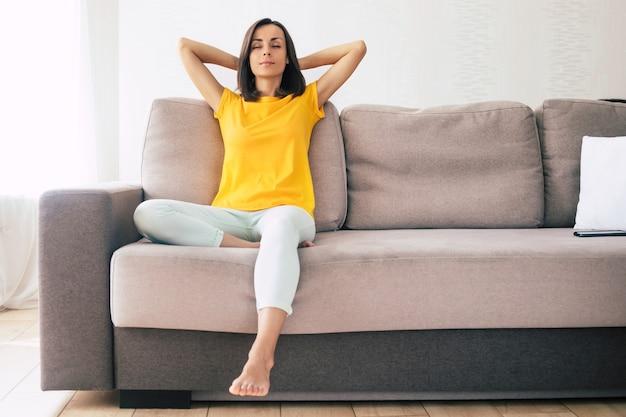 아름 다운 진정 자신감 갈색 머리 여자는 휴일 동안 집에서 소파에 쉬고있다