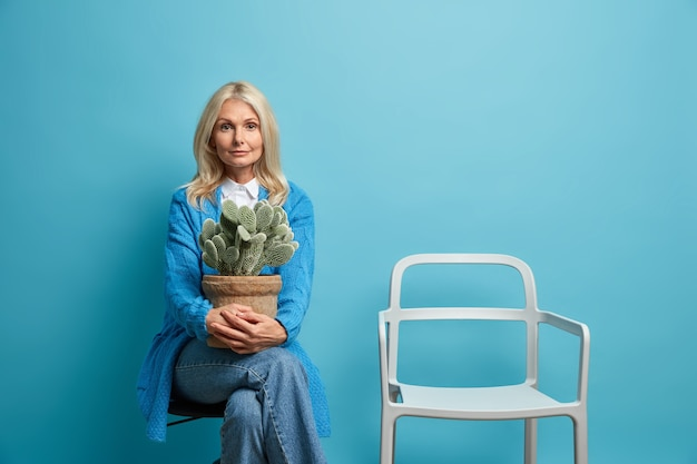 Beautiful calm confident wrinkled european woman feels nostalgia melancholy holds with potted cactus poses with empty chair