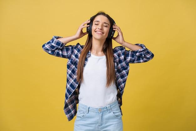 노란색 배경에 눈을 감고 헤드폰으로 음악을 듣고 있는 아름답고 차분한 젊은 여성. 확대