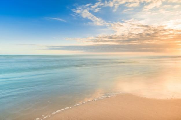 작은 파도와 함께 열대 해변에서 아름다운 고요 일몰은 편안한 시간에 낙원처럼 보입니다.
