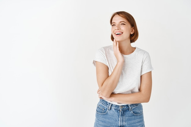 Beautiful candid girl with perfect smile, laughing and looking aside, touching natural beauty face without make-up, standing against white wall