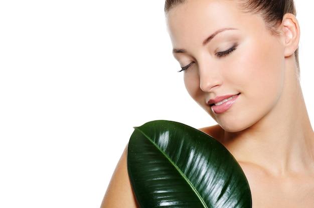 彼女の裸の体に目を閉じて緑の新鮮な葉を持つ美しい率直な女性の顔