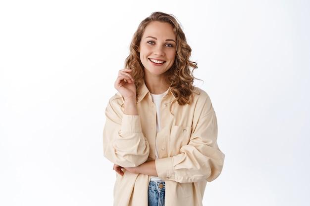 Красивая откровенная женщина с вьющейся прической, улыбается и выглядит счастливой спереди, оптимистично стоя у белой стены
