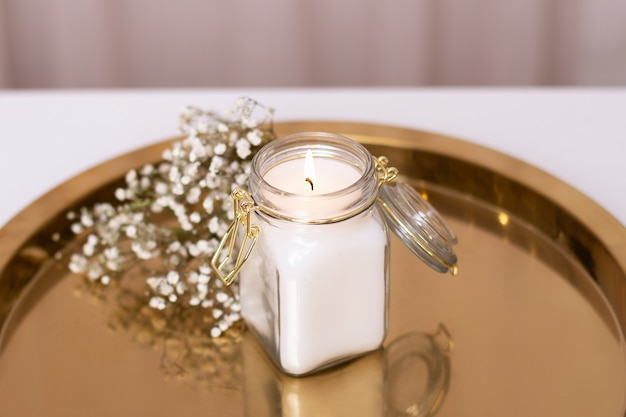 Beautiful candle light with white flowers on golden plate, romantic