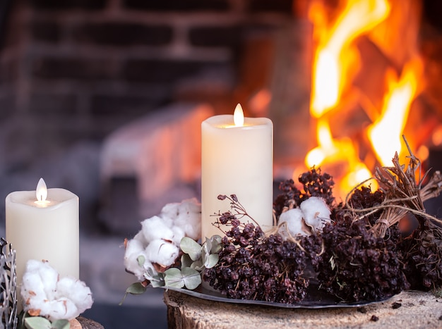 Beautiful candles decorated with dried flowers and cotton are burning near the fireplace. the concept of a cozy holiday.