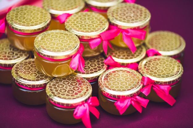 ピンクの弓で飾られた蜂蜜と美しい缶
