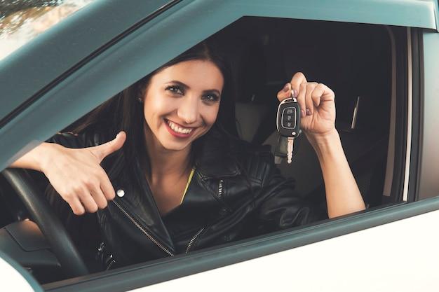新しい車のキーと車を見せて笑っている美しい車の運転手の女性。自動車に座って、笑顔で鍵をデモンストレーションする白人の女の子。車の女性の所有者。女性は自動車を購入して喜んでいます。