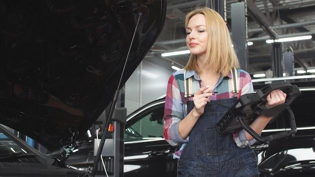 제복을 입은 아름다운 자동차 정비공 여자는 휴대용 컴퓨터의 자동차 진단에 종사하고 있습니다