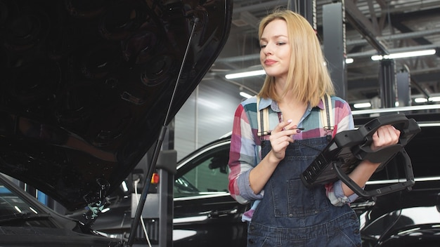 Beautiful car mechanic woman in uniform is engaged in car diagnostics on a portative computer
