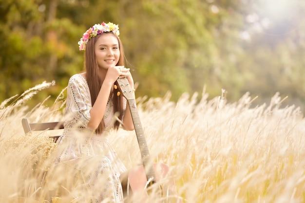 Красивая беззаботная азиатская женщина на лугу.