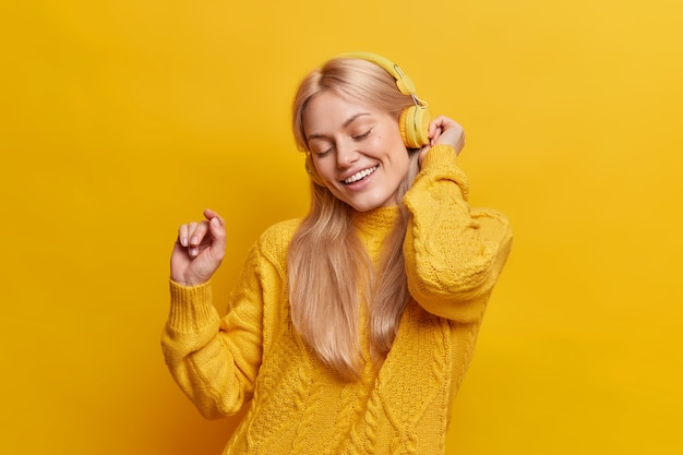 아름다운 평온한 금발의 여자 춤은 헤드폰에서 즐거운 음악으로 이완 팔을 제기 유지