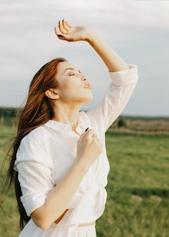 Beautiful carefree long hair asian girl in white clothes on field at sunset