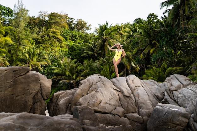Красивая беззаботная молодая женщина в желтом бикини на тропическом острове