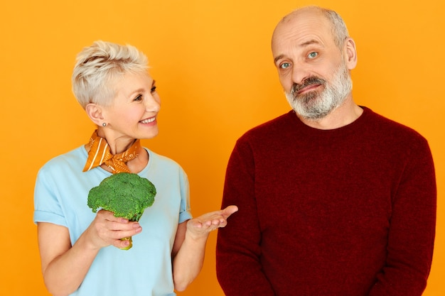 Beautiful caring mature woman holding broccoli offering healthy meal to her sick husband pensioner who is on strict vegetarian diet. displeased elderly man dislikes eating veggies