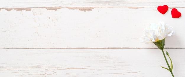 밝은 나무 테이블, 복사 공간, 평면 평신도, 평면도에 고립 된 흰색 빈 카드와 함께 아름 다운 카네이션과 하트 모양, 모의