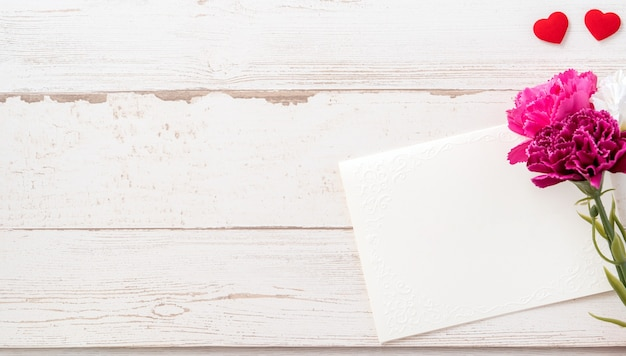 밝은 나무 테이블, 복사 공간, 평면 평신도, 평면도에 고립 된 흰색 빈 카드와 함께 아름 다운 카네이션과 하트 모양