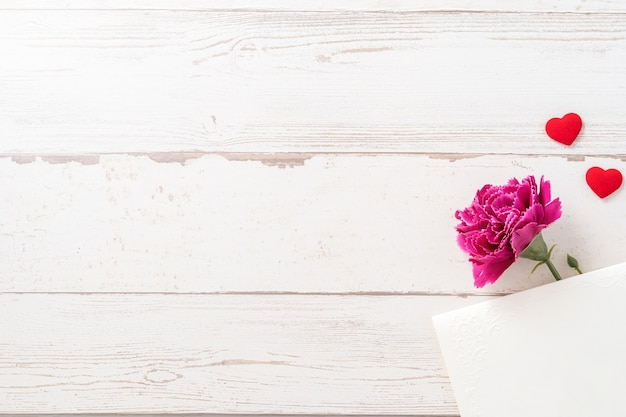 Beautiful carnations and hearts shape with white empty card isolated on a bright wooden table, copy space, flat lay, top view, mock up
